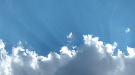 Puffy white clouds and scattered light rays against blue sky
