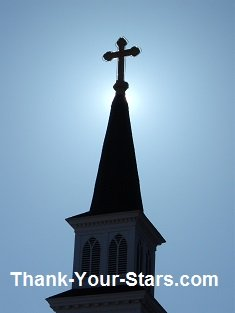 Cross on Church Steeple backlit by the sun with a blue sky background